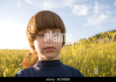seven year old boy closing his eyes and listening to the birds sing in a field of wildflowers, Pagosa Springs, Colorado - Stock Photo