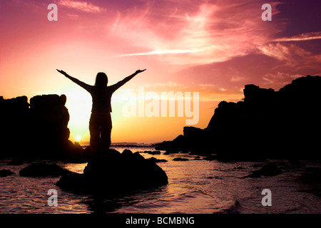 Woman silhouette relaxing at the sunset - Stock Photo