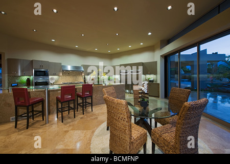 Large modern kitchen area with red bar stools at island breakfast table and retractable glass wall behind - Stock Photo
