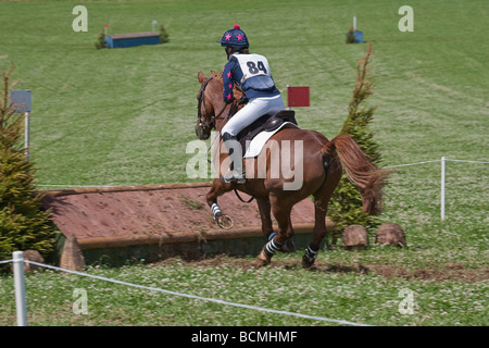 Teenage girl on brown pony/horse jumping fence in cross-country event. - Stock Photo