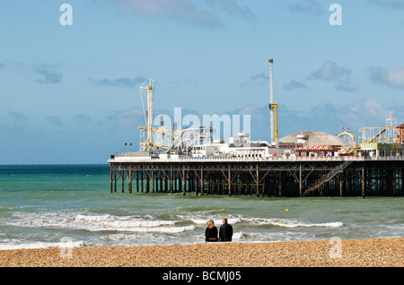 Two people sitting on the shingle beach near Brighton Pier in Sussex.  Photo by Gordon Scammell - Stock Photo
