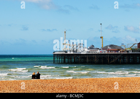 Two people sitting on the shingle beach near the pier in Brighton in Sussex.  Photo by Gordon Scammell - Stock Photo