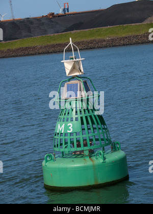 Modern green buoy in the port of Rotterdam marking the shipping lane with solar panels to power its transmitter - Stock Photo
