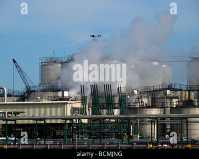 Petrochemical plant in the port of Rotterdam Zuid Holland the Netherlands with blue sky and cloud escaping - Stock Photo
