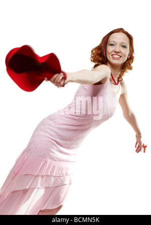 Young smiling woman throwing a red hat - Stock Photo