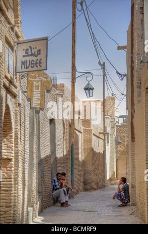 Three men sit in an alley in Tozeur, Tunisia's 14th century Ouled El Hadef quarter. - Stock Photo