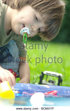 Child little boy CLOSE UP playing with toys in the garden - Stock Photo