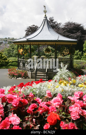 City of Truro, England. Flower beds in full bloom in Truro's Victoria Gardens, with the Victorian bandstand in the - Stock Photo