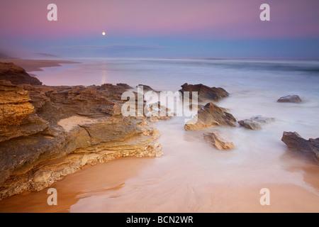 Full moon rising against sunset sky over  rocky beach. Garden Route - Stock Photo