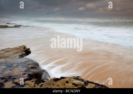 Water cascading off coastal rocks under dramatic sky. Garden Route - Stock Photo