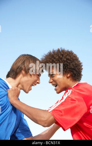 Two opposing team members screaming at each other, foreheads touching - Stock Photo