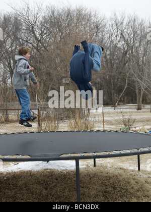 Two Children Jumping on Trampoline - Stock Photo