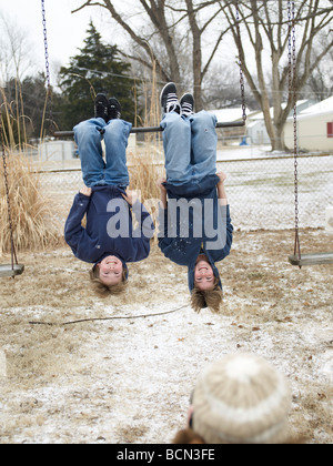 Two Boys Hanging Upside Down From Bar - Stock Photo