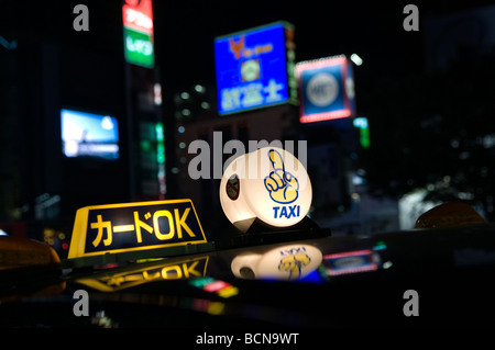 Illuminated taxicab toplight sign with neon lights and advertisement signs in Tokyo Japan - Stock Photo