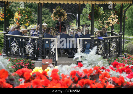 City of Truro, England. Flower beds in full bloom in Victoria Gardens, with a brass band playing in the Victorian - Stock Photo