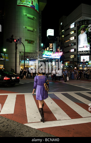 People crossing a pedestrian crossing in Shibuya commercial district Tokyo Japan - Stock Photo