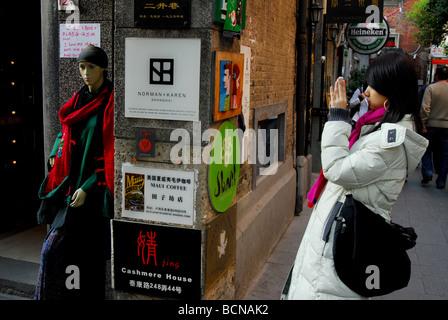 Young Chinese woman taking photo in Xintiandi, Shanghai, China Stock Photo