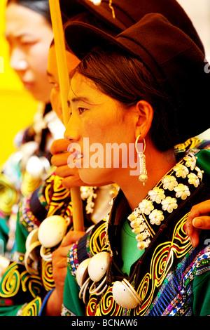 Yi minority women in elaborate ethic costume holding yellow umbrella, Torch Festival, Liangshan Yi Autonomous Prefecture, - Stock Photo
