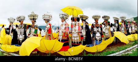 Yi Minority women in elaborate ethnic costume in a dance formation, Torch Festival, Liangshan Yi Autonomous Prefecture, - Stock Photo