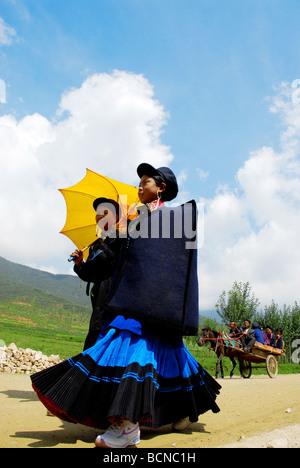 Yi minority young women in ethnic costume while wearing modern tennis shoes, Torch Festival, Liangshan Yi Autonomous - Stock Photo