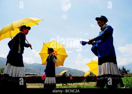 Yi minority young women in ethnic costume while holding yellow umbrella, Torch Festival, Liangshan Yi Autonomous - Stock Photo
