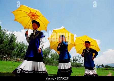 Yi Minority young woman in ethnic costume while holding yellow umbrella, Torch Festival, Liangshan Yi Autonomous - Stock Photo