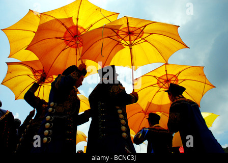 Yi Minority young woman in ethnic costume while holding yellow umbrella in a dance formation, Torch Festival, Liangshan - Stock Photo