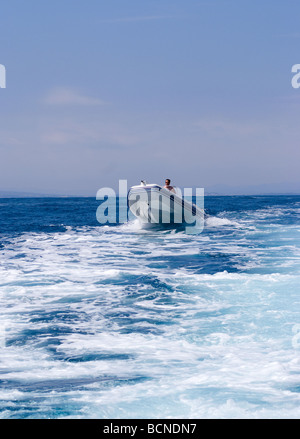 Inflatable Rib or Zodiac Speedboat Passing Wake of Motor Cruiser in Mediterranean Sea near Cadaques Costa Brava - Stock Photo