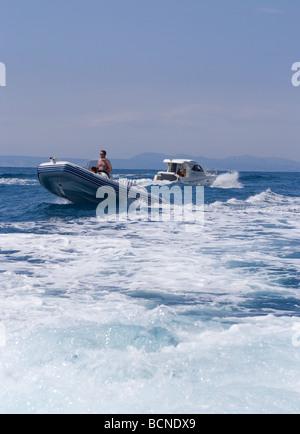 Inflatable Rib or Zodiac Speedboat Passing Wake of Motor Cruiser in Mediterranean Sea near Cadaques Costa Brava - Stock Photo