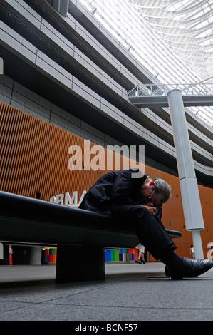A business man sleeping inside the Tokyo international forum cultural center in Marunouchi district Tokyo Japan