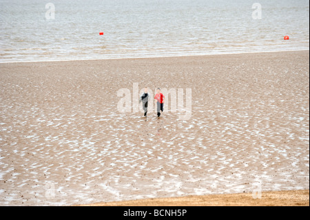 Two boys running on cleethorpes beach - Stock Photo