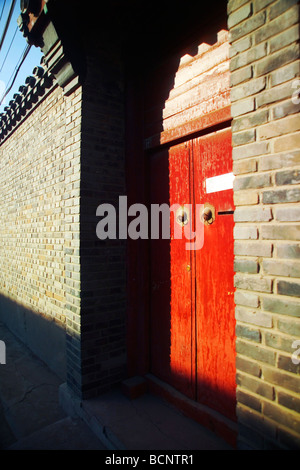 Red front gate of a courtyard house in a typical hutong, Beijing, China - Stock Photo