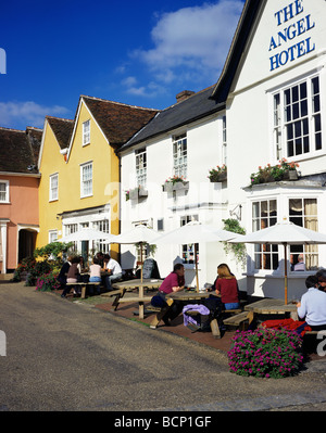 Visitors enjoying a drink outside the Angel Hotel in the old Suffolk village of Lavenham - Stock Photo