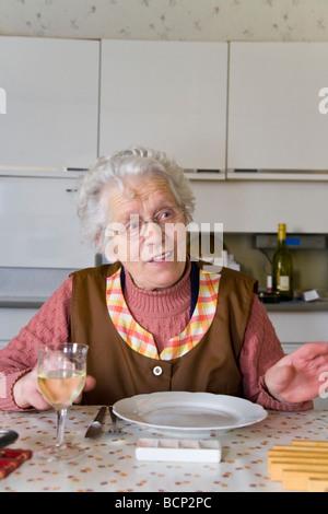 Frau in ihren Siebzigern sitzt in der Küche am gedeckten Mittagstisch