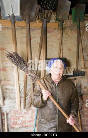 Frau in ihren Siebzigern mit Kopftuch steht vor einer Wand mit Werkzeugen und hält einen Reisigbesen - Stock Photo
