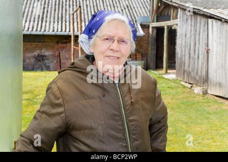 Frau in ihren Siebzigern mit Kopftuch posiert vor ihrem Bauernhof - Stock Photo