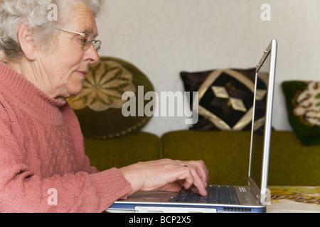 Frau in ihren Siebzigern sitzt im Wohnzimmer am Laptop