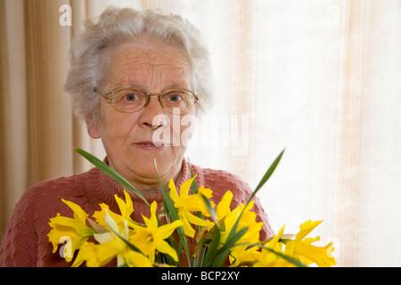 Frau in ihren Siebzigern steht im Wohnzimmer und hält einen Strauß Osterglocken Narcissus pseudonarcissus  - Stock Photo