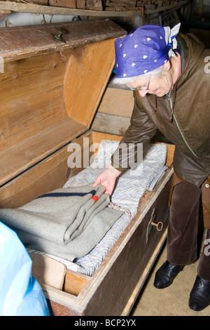 Frau in ihren Siebzigern mit Kopftuch schaut in eine große alte Wäschetruhe - Stock Photo