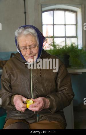 Frau in ihren Siebzigern mit Kopftuch sitzt in der Waschküche und schält sich einen Apfel - Stock Photo