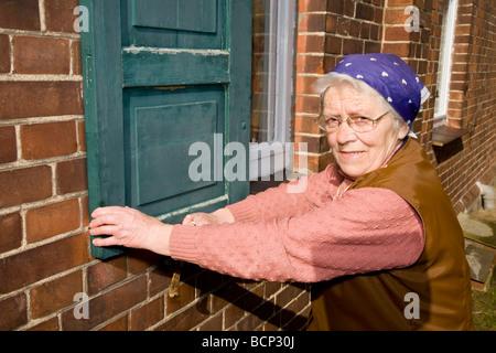 Frau in ihren Siebzigern mit Kopftuch schließt die Fensterläden eines Hauses - Stock Photo