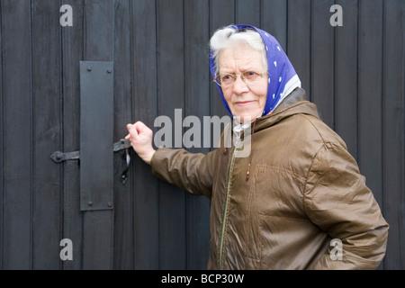 Frau in ihren Siebzigern mit Kopftuch schließt den Riegel am Scheunentor auf ihrem Bauernhof - Stock Photo