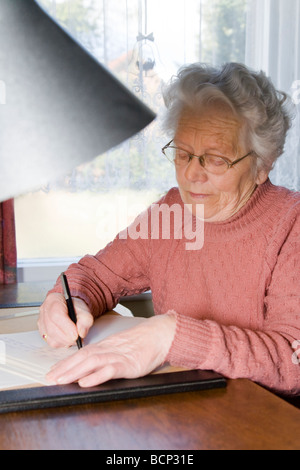 Frau in ihren Siebzigern sitzt am Schreibtisch und schreibt einen Brief
