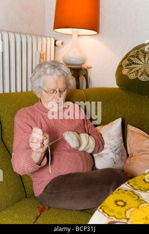 Frau in ihren Siebzigern sitzt im Wohnzimmer und stopft Wollsocken