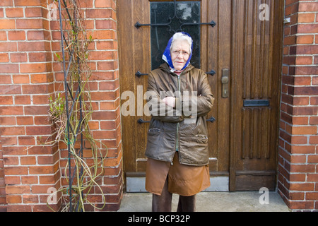 Frau in ihren Siebzigern mit Kopftuch steht mit verschränkten Armen vor ihrer Haustür - Stock Photo