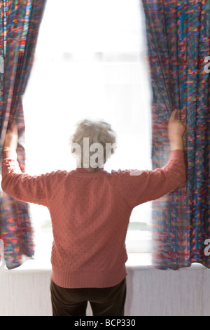 Frau in ihren Siebzigern steht morgens am Fenster und zieht die Gardinen zur Seite - Stock Photo
