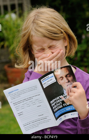 Swine flu information leaflet being read by sneezing child - Stock Photo