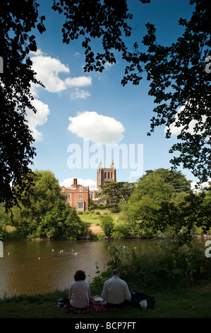 Hereford Cathedral, two people sitting on the banks of the River Wye in  Hereford city Herefordshire England UK - Stock Photo