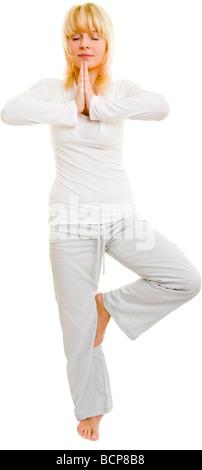 Junge Frau steht auf einem Bein mit geschlossenen Augen und meditiert