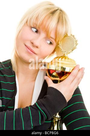 Junge Frau in Sportkleidung umarmt einen Pokal - Stock Photo